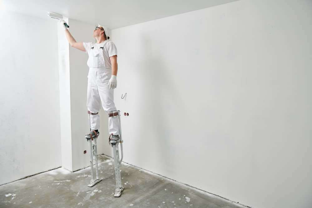 Painter on stilts painting
