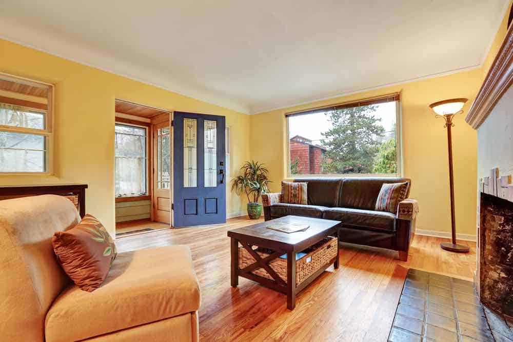 Yellow living room with blue door and wood floors.