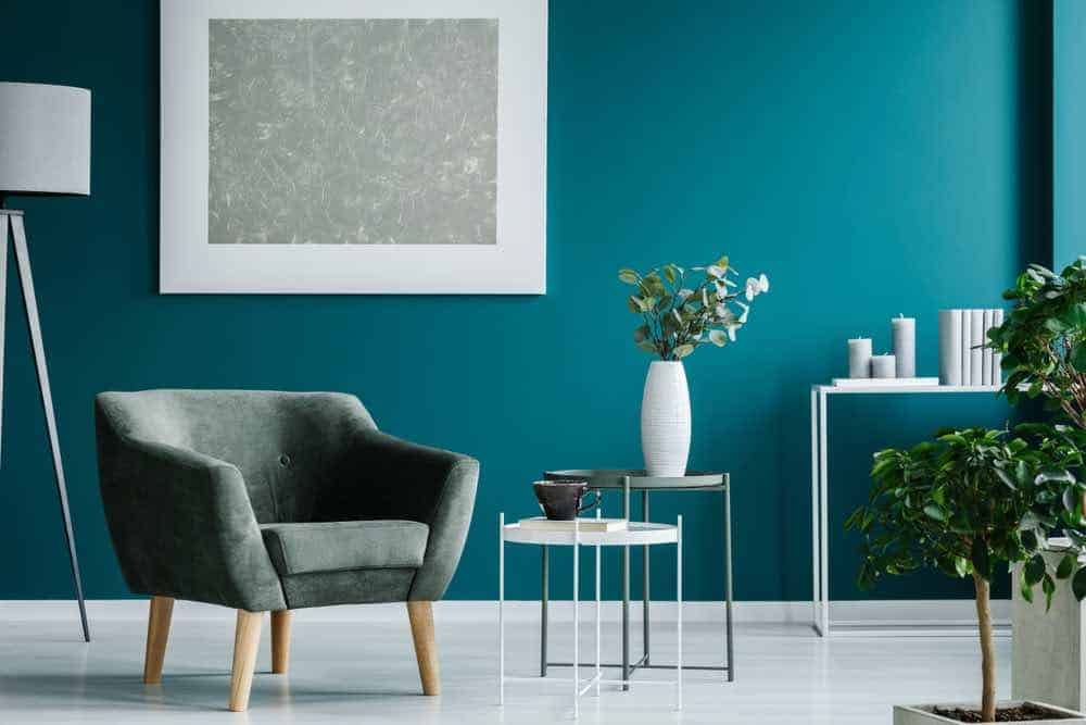 Green armchair against aqua wall with white decor
