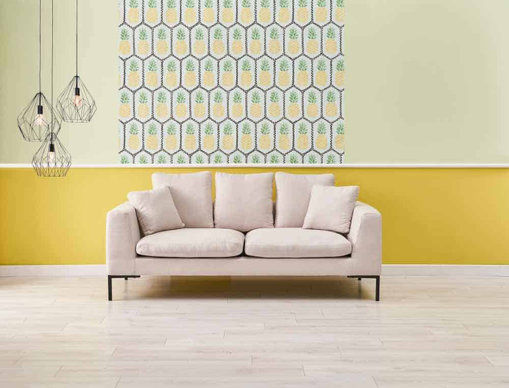 Modern yellow living room with white couch and patterned accent wall