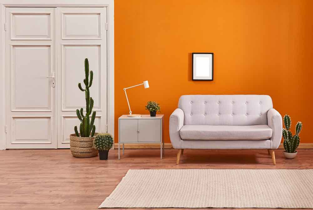 Orange room with white sofa and wood floors