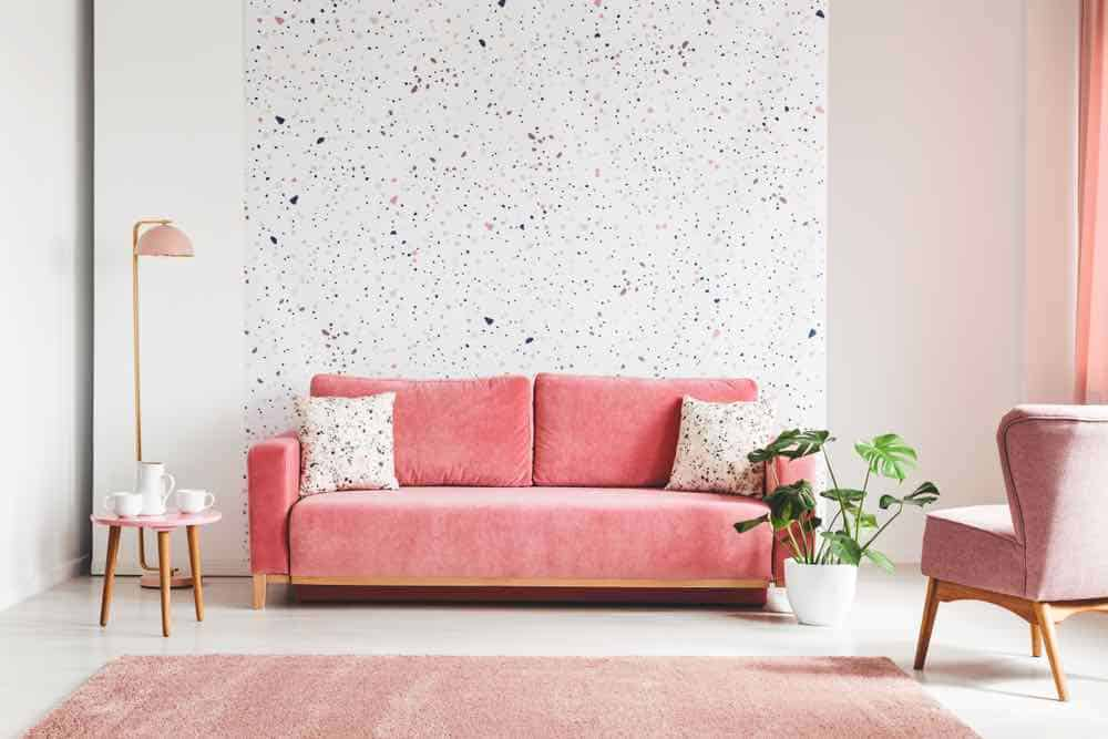 speckled pattern wall with pink velvet couch