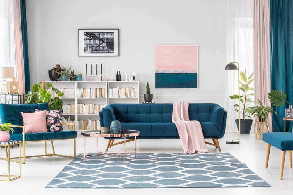 White living room with blue couch and pink accents