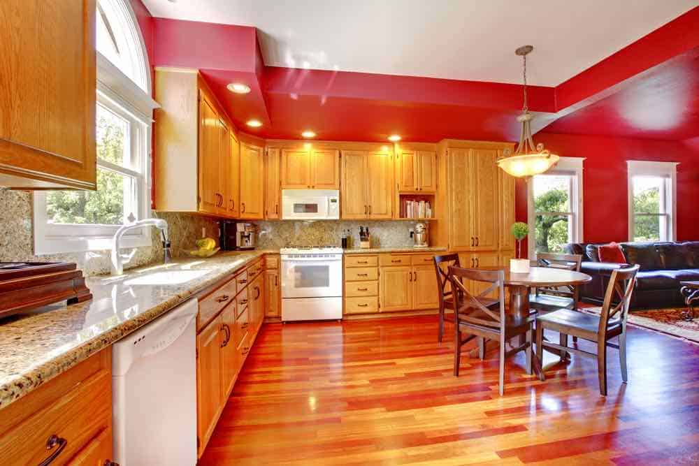 Kitchen with crimson red painted walls, oak cabinets, wood floor, and granite counter top