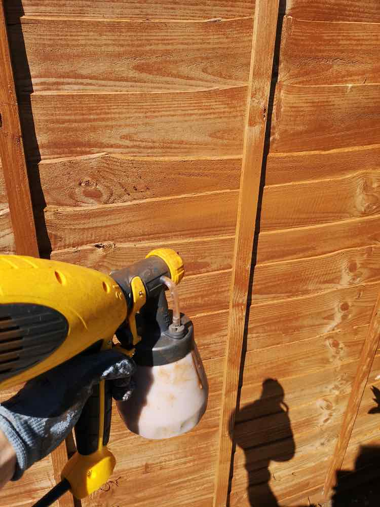 Using a Wagner Power Sprayer to spray stain onto a fence.