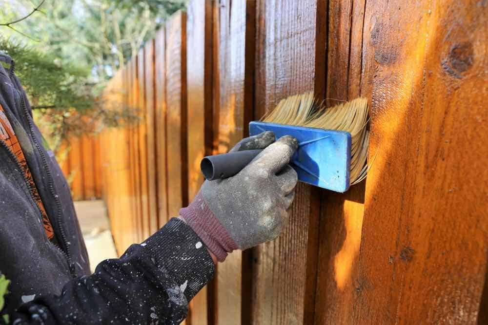 Staining a fence with a stain brush