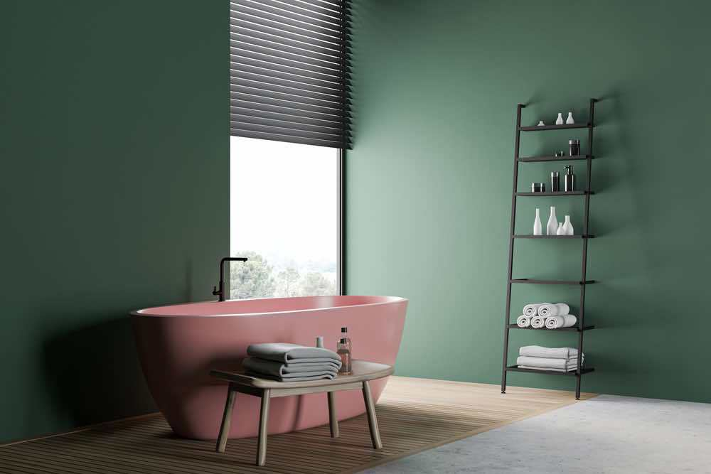 A sophisticated bathroom with lots of natural light, dark green painted walls, and pink tub.