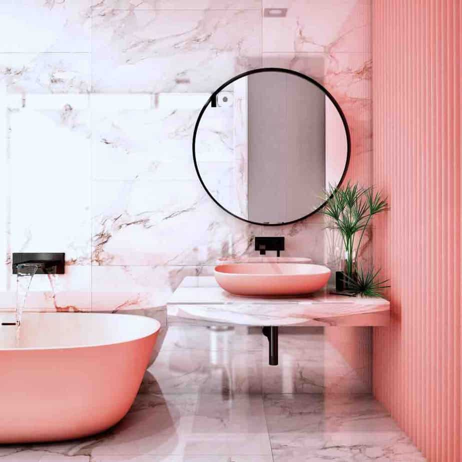 A stylish bathroom with pink wall, sink, and tub and pink marble tiling.