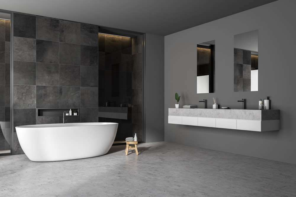 A glossy contemporary bathroom with gray wall, gray tiling, and gray stone floor.