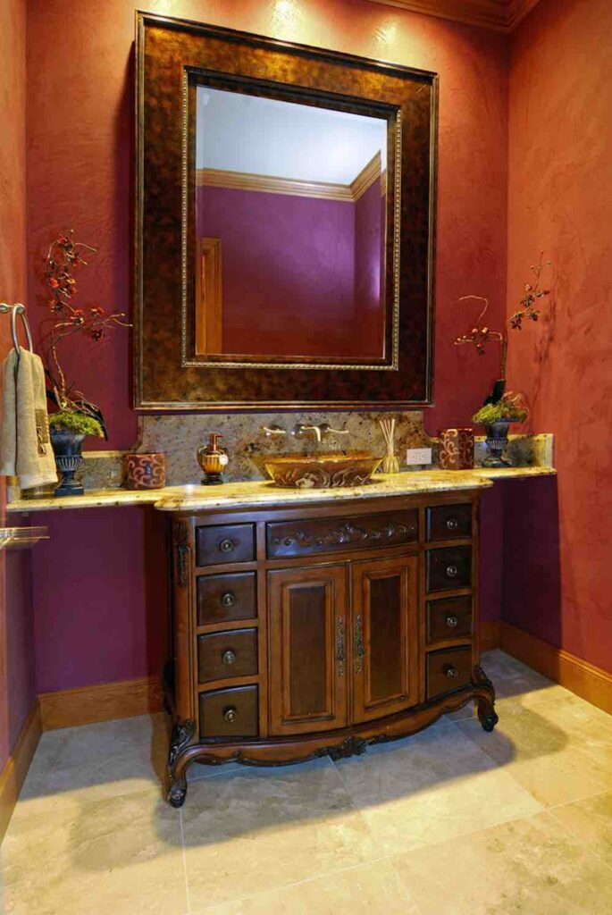 A compact powder room with large framed mirror, ornate vanity, and dark red painted walls.