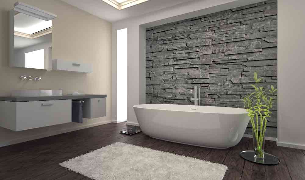 A modern bathroom with pale beige walls and natural stone tiling.