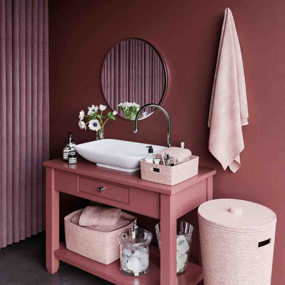 A monochromatic bathroom with pink vanity, pale pink woven baskets, and mauve painted walls.