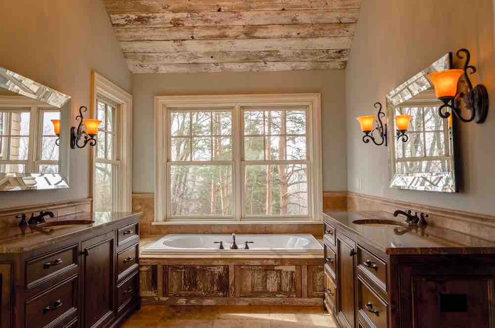 A bathroom with lots of natural light, and evergreen trees outside the window. It has wood accents and dark beige paint.