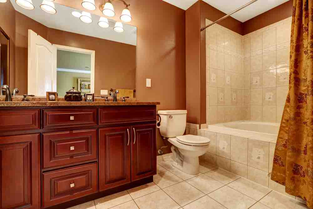 A typical bathroom with light tiles, umber walls and granite vanity.
