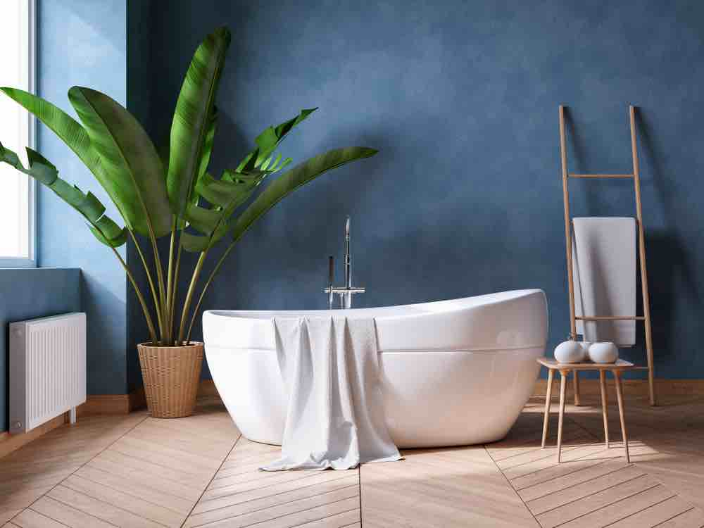 A white stand-alone tub with a potted plant and dark blue faux-finish walls.