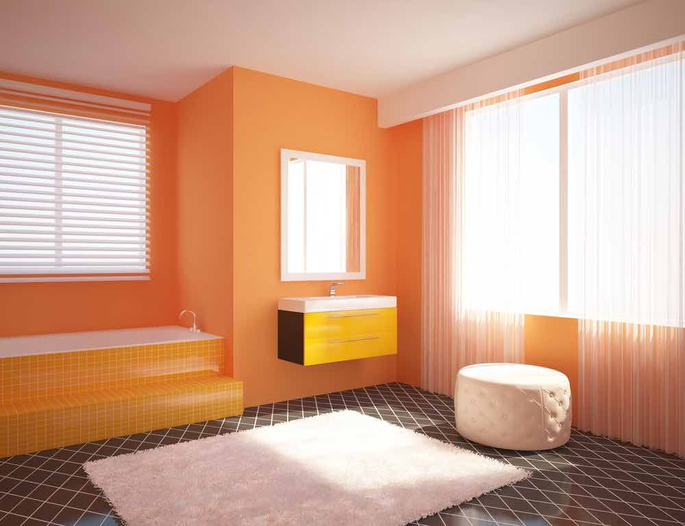 A super well lit contemporary bathroom with orange tiled tub and vanity and tangerine painted walls.