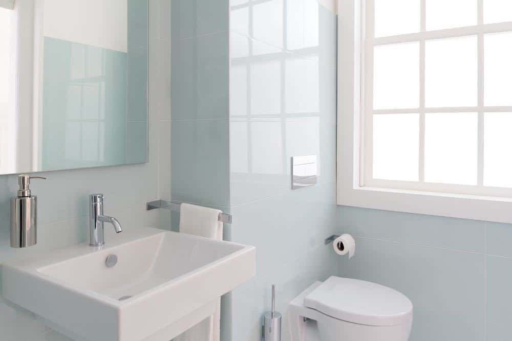 A bright bathroom with pale blue walls and white accents.