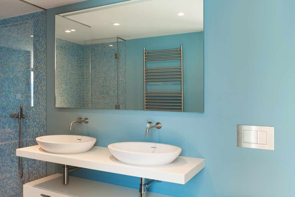 His and hers sinks set on a white vanity with robin's egg blue painted walls.
