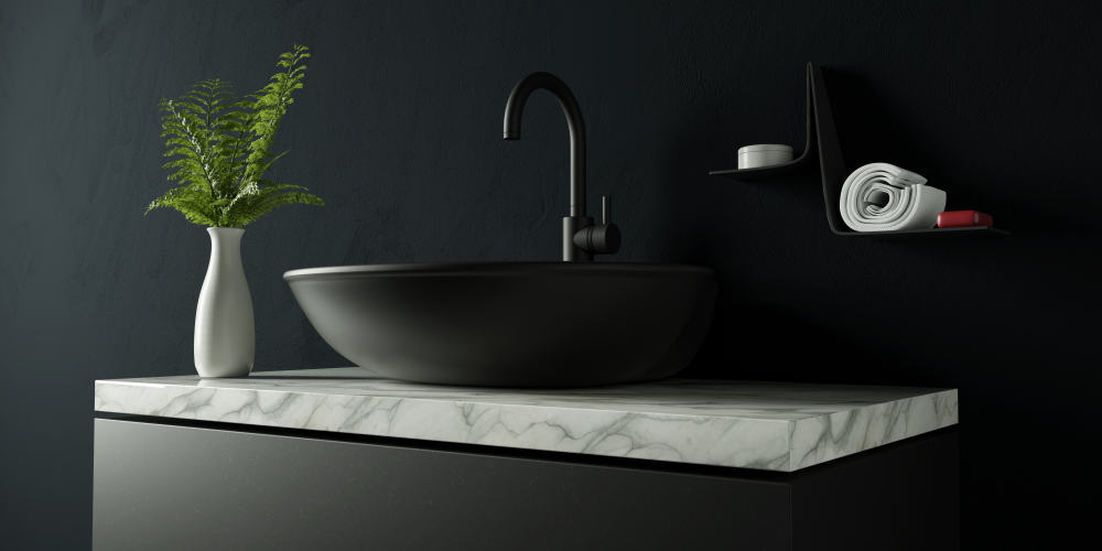 A matte black sink and vanity with white marble countertop and black painted wall.