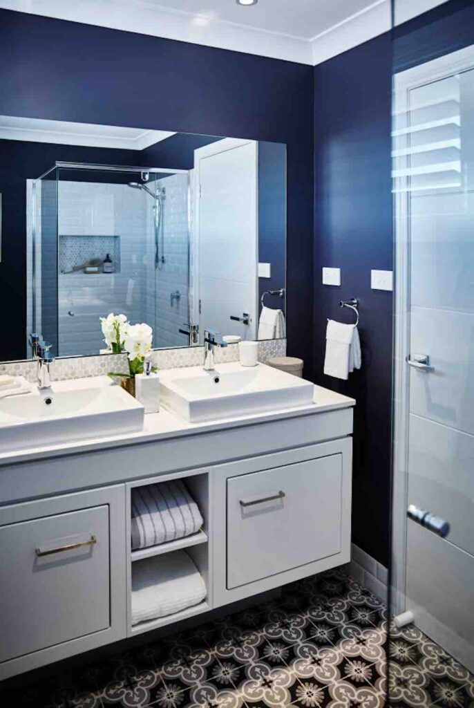 A fresh modern bathroom with dark blue walls and white finishes.