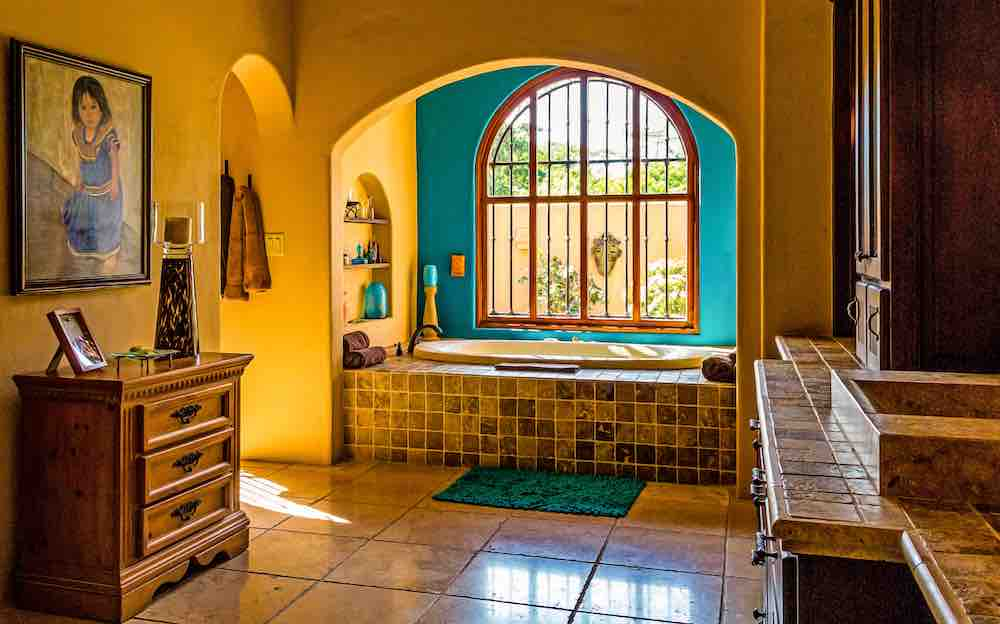 A southwest inspired bathroom with high contrast turquoise and yellow stucco walls and brown tiles.