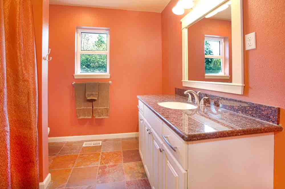 A traditional bathroom with coordinated red and orange floor, vanity, shower curtain and dark orange painted walls.