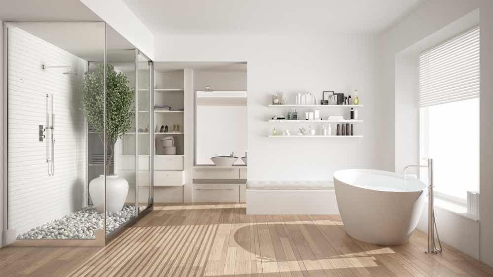 A super-white minimalist Scandinavian bathroom with natural wood floors, painted walls, and a potted tree in the shower.