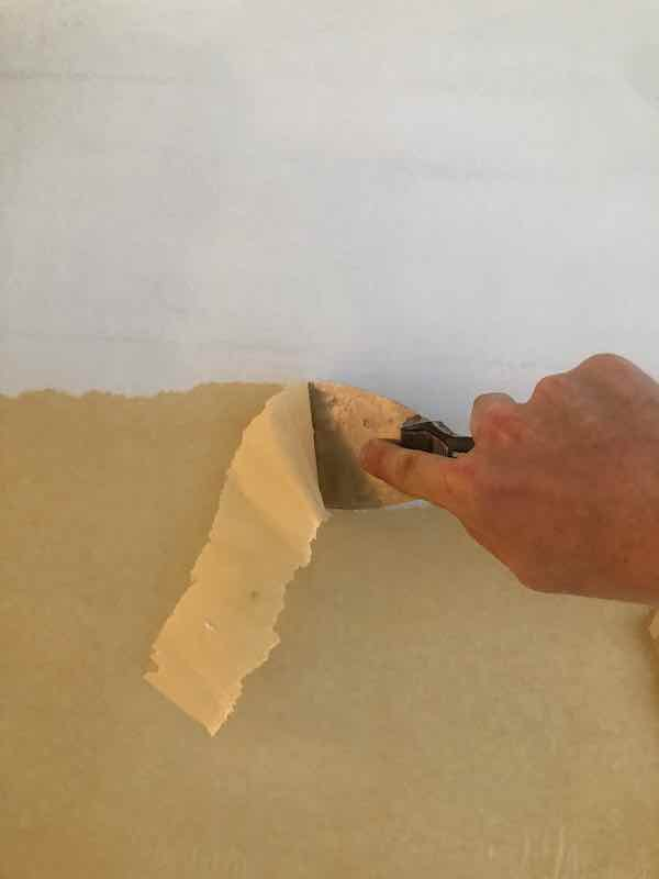 Scraping off the wallpaper backing and paste.