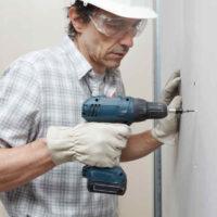man using a cordless drill to hang drywall