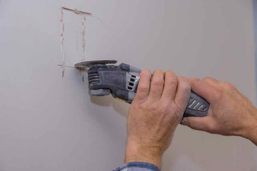 person using an oscillating tool to cut out drywall for electrical outlet