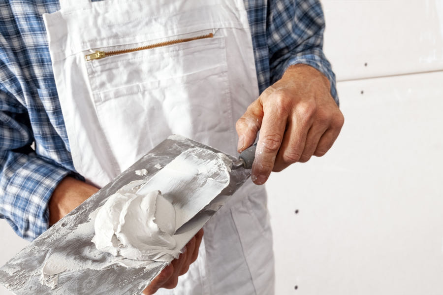 person mixing joint compound to apply to new drywall