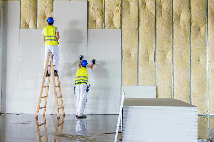 workers assemble drywall while standing on a ladder