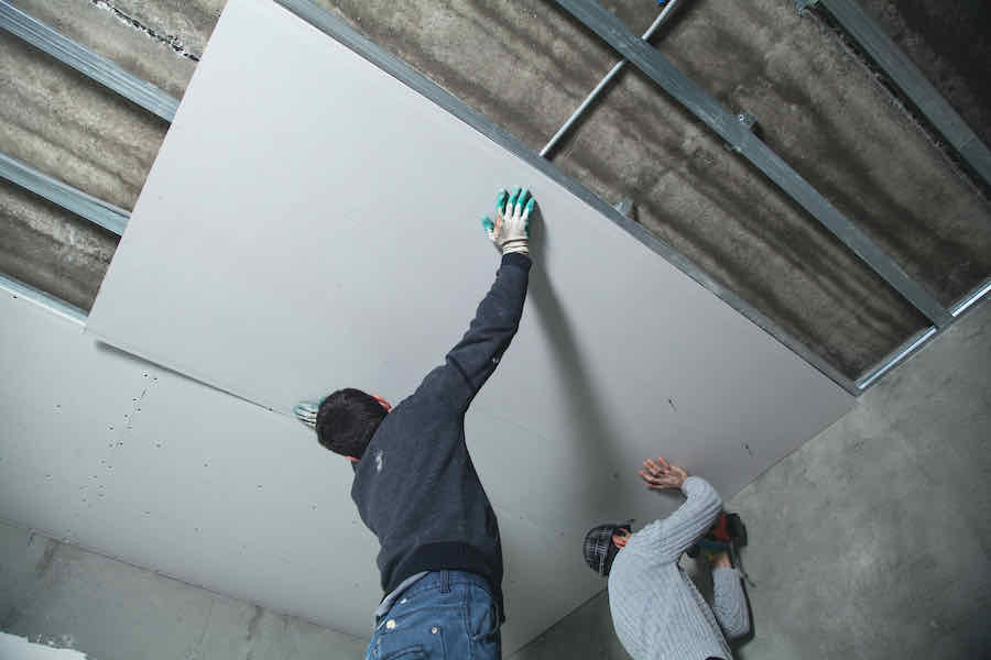 workers hanging drywall panel on ceiling