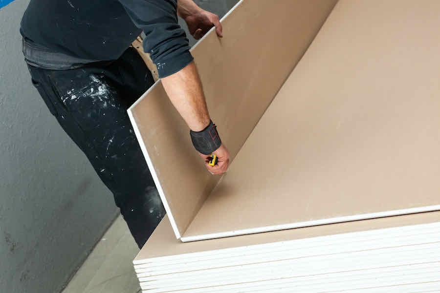 person scoring a drywall panel