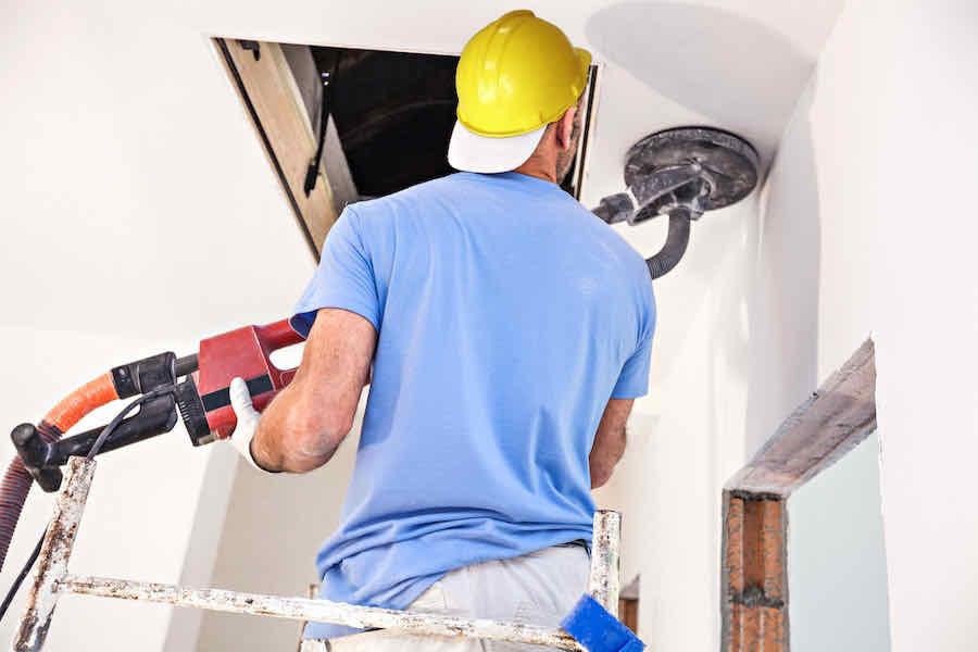 worker using a drywall sander