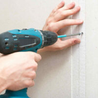 person fastens drywall nails with a screwdriver