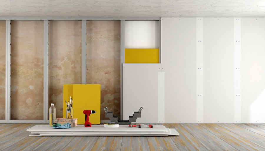 drywall tools set on top of drywall panels